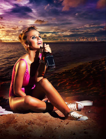 Beautiful young woman drinking booze on beach - alcoholism or other addiction photo