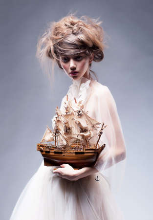 Creative art  Sophisticated young stylish woman in white vintage dress with retro boat posing photo