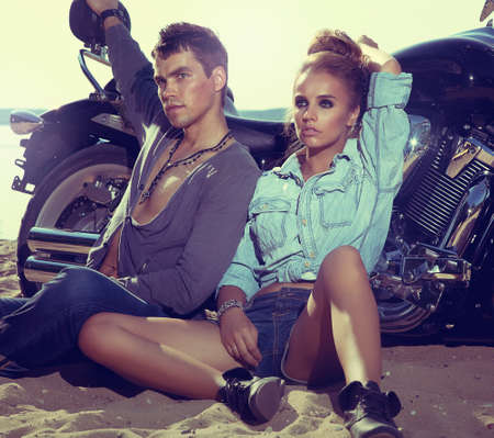 Two people and bike  fashion woman and man sitting by motorbike and resting  Adventure and vacations concept photo