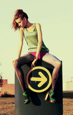Fashion woman sitting on road sign indicating direction guide icon - arrow  Grunge, sepia style photo