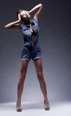 salopette: Adolescent mannequin en jeans posant sur le podium - torse beaut� fille mince