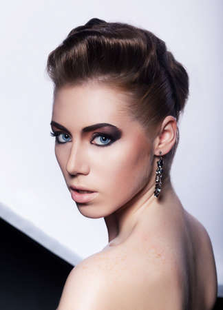 Portrait of beautiful fashionable woman with earrings - stylish styling coiffure  hairstyle  photo