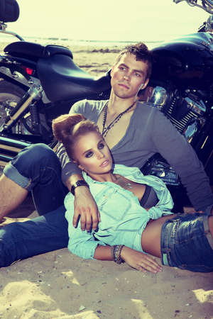 Young couple on sand of beach relaxing over background of a beautiful bike Stock Photo - 15025326