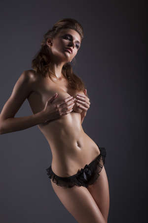 Nude young woman covering her natural breasts with hands over black background Stock Photo - 15489548