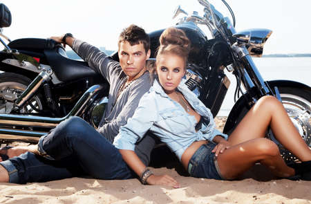 Extreme couple sitting by motorcycle on the beach  Adventure and travel concept photo