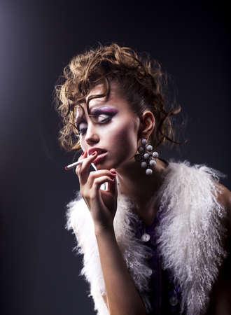 Elegant brunette woman smoking a cigarette on black background - bad habits Stock Photo - 15488766