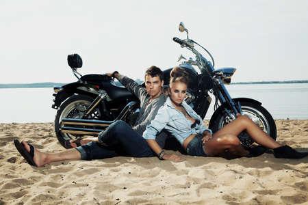 motociclista: Giovani piloti bello ragazzo e ragazza che si siedono insieme sulla spiaggia di sabbia in bicicletta bella - viaggi