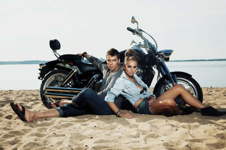 Young handsome boyfriend and girlfriend riders sitting together on sand beach by beautiful bike - travel photo