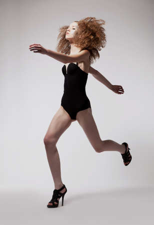 Redhead sporty fashion woman running in black lingerie isolated Stock Photo - 15331983
