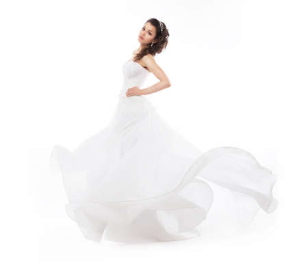 Brunette bride woman in bridal fashion white dress running - studio shot photo