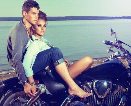 boy romantic: Beautiful couple family sitting on lake shore on motor bike Stock Photo