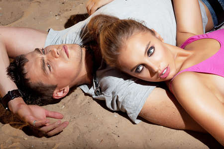 Portrait of beautiful young couple resting on sand lying - satisfaction photo