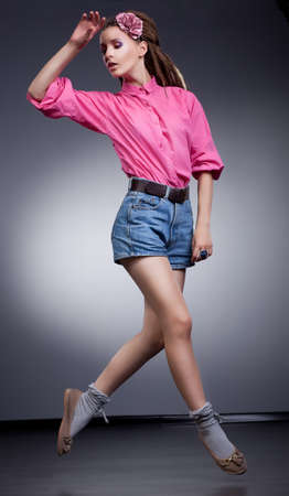 Motion - active girl in elegant jeans shorts, studio shot photo