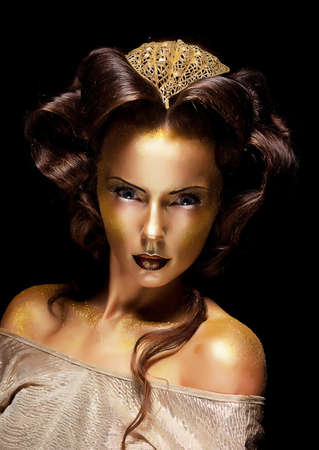 Dramatic style  Woman gilded gold face - theater luxury make up photo