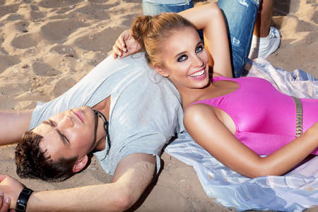 Lole - two romantic people lying together on sand Stock Photo - 15483189
