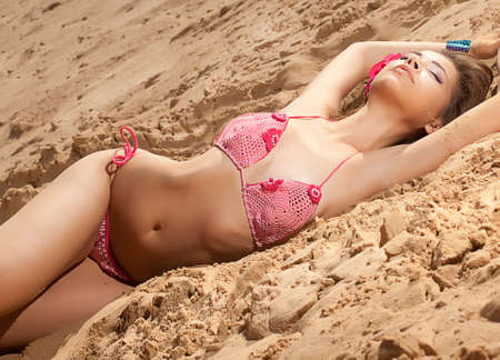Pretty girl in bikini on sand sunbathing and lying photo