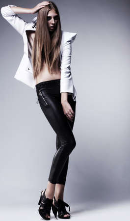 Young brunette lady in black leggings posing on grey background  Glamour, beauty style photo