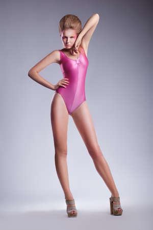 Beautiful sexy girl with long hair wearing pink swimsuit and heels photo