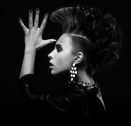 Strange stylish punk female saluting and gesturing, creative hairstyle Stock Photo
