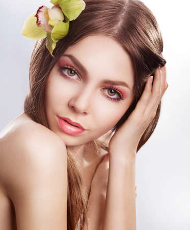 Beautiful fashion model woman with orchid flower  Sensuality photo