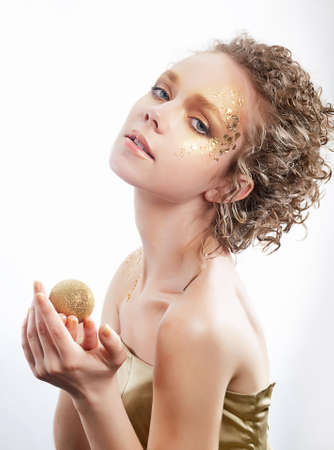 bodyart: Fashion woman - beauty gilded golden make-up. Luxurious young face, curly hair