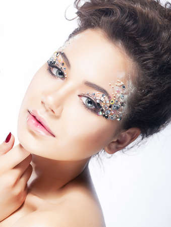 Young beauty woman touching her beautiful face. Bright coiffure and make-up photo