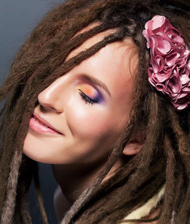 Dreadlocks hairstyle. Emotions. Fashion female  hairstyle. Flower Stock Photo - 15867514