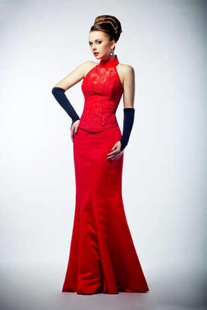 long shot: Beauty bride in long weddingred dress and black gloves - studio shot