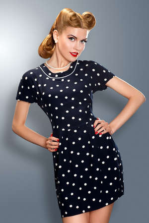 Pin-up girl in retro vintage old-fashioned dress in romantic pose