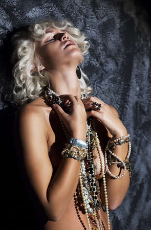 young girl nude: Nude young female blonde with necklace in erotic pose - studio shot