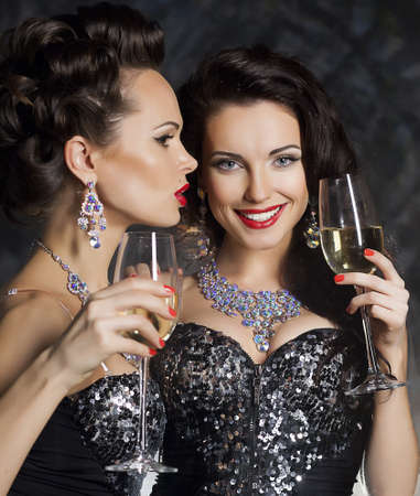 Christmas. Banquet. Two festive young fashion women with wine glasses of champagne photo