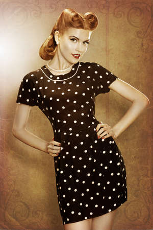 pin up: Pin-Up girl in classic fashion polka dots dress posing - grunge Stock Photo