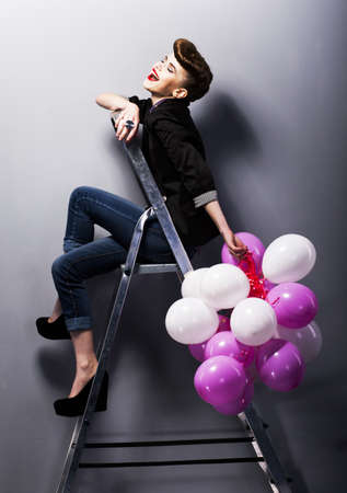 pinup girl: Pretty cheerful fashion retro model teen girl laughing on ladder in studio with balloons