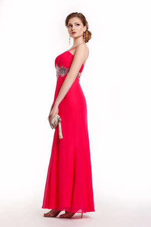 evening gown: Fashion young female in modern red long dress with handbag posing