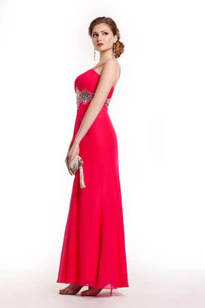 traje de gala: Moda femenina joven en el moderno vestido largo de color rojo con el bolso posando Foto de archivo