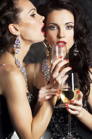 Christmas. Banquet. Two festive young fashion women with wineglasses of champagne photo