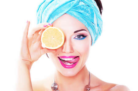 Cheerful young woman holding juicy delicious lemon (orange). Natural organic food concept photo