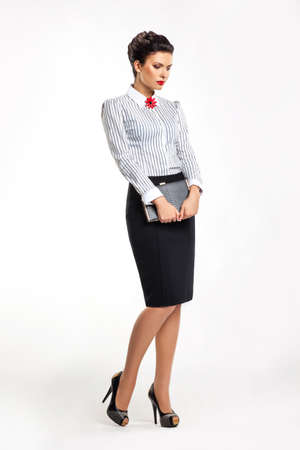 stern: Thoughtful businesslady in fashion skirt and blouse with book dreaming