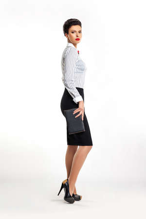 secretary skirt: Full length portrait of confident young business woman secretary with handbag sideways