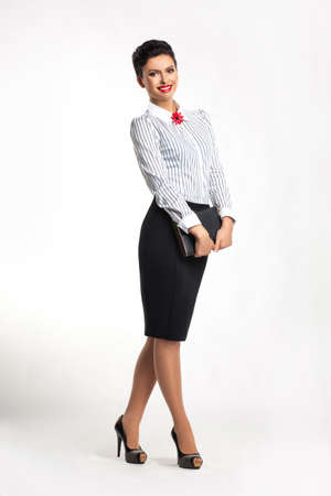 scratchpad: Smiling stylish successful businesswoman with notepad standing