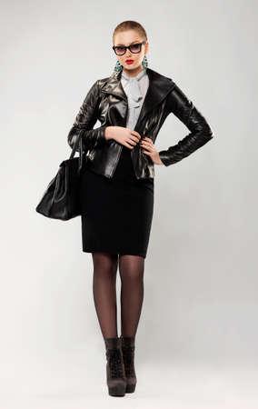 handbag model: Fashionable confident trendy woman in sunglasses and handbag in studio