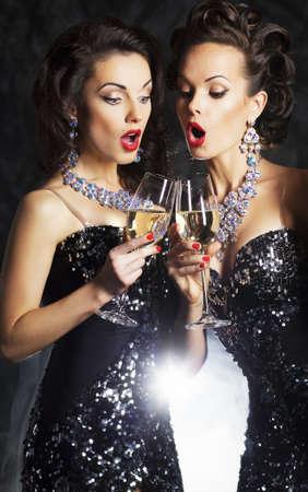 festive occasions: Un par de mujeres de la moda con las flautas de champ�n espumoso cantando canciones de Navidad Foto de archivo