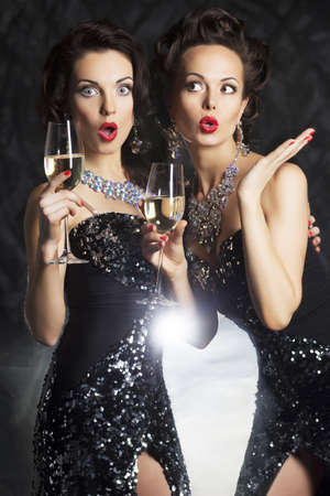 fancy dress party: Congratulation! Fashion women with wine glasses of champagne Stock Photo