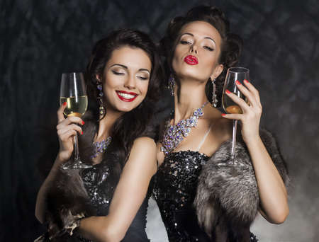 Happy New Year - two women with wine glasses smiling Stock Photo