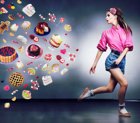 Escape. Resolute running woman refuses to eating tasty cakes and chocolate. Diet concept photo