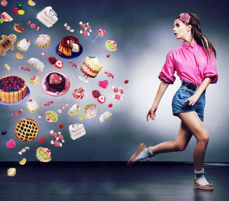 �sweets: Escape. Resuelto mujer corriendo niega a comer las deliciosas tartas y chocolate. Dieta concepto Foto de archivo