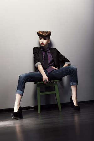 Pin up retro woman sitting in jeans and stylish jacket. Bright hairstyle photo
