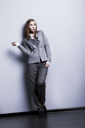 Fashion style. Young beautiful womqn in gray suit posing in studio photo