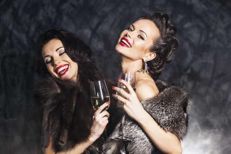 Nightlife. Jonge happy fashion vrouwen vieren de gebeurtenis in nachtclub. Congrats!