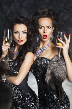 hristmas: Two beautiful young women drinking champagne in night club. Merry Сhristmas! Stock Photo